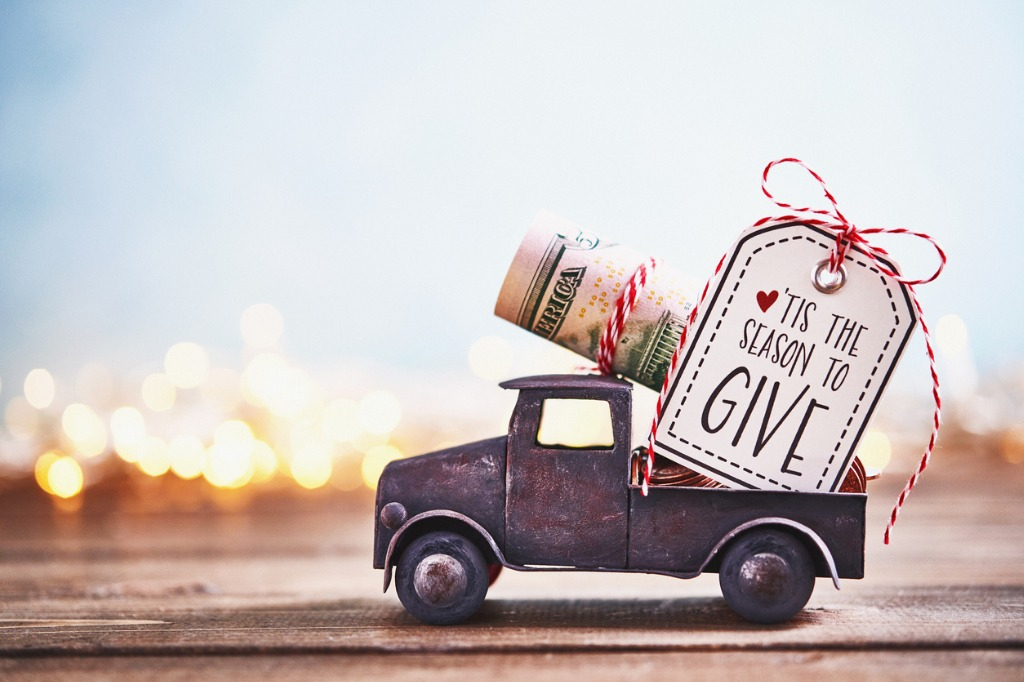 season-to-give-truck-carrying-roll-of-dollars-with-holiday-background-picture-id1166729754